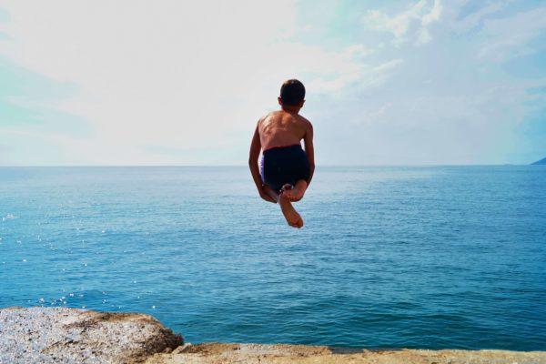 Ένα αγόρι κάνει βουτιά στη θάλασσα στις καλοκαιρινές διακοπές